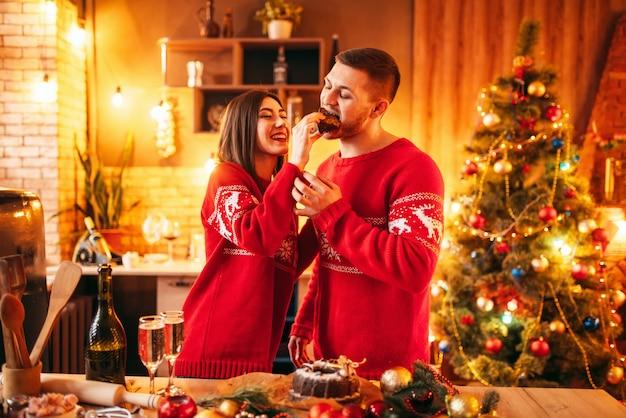 幸せな愛のカップル、妻は夫にクリスマスケーキ、お祝いの食べ物を供給しています。一緒にクリスマスのお祝い、若い家族の幸せ