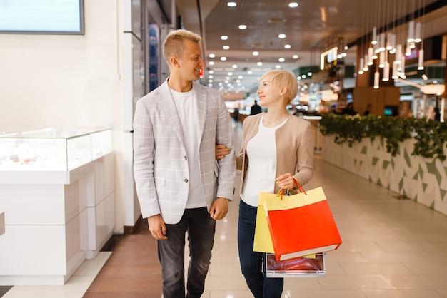 Счастливая влюбленная пара с хозяйственными сумками в ювелирном магазине.