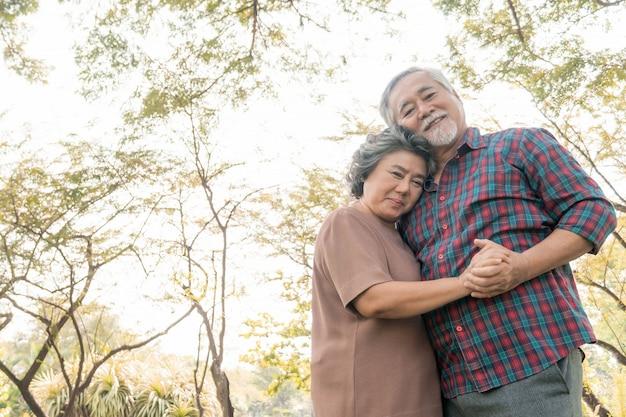 Happy love elderly senior couple hugging smile face , senior couple old man and senior woman relaxing hug in park