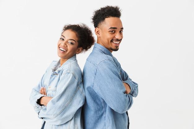 灰色の壁の上にお互いに戻って立っているデニムシャツで幸せな素敵なアフリカカップル