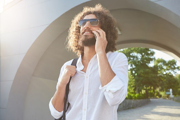 Happy lovely bearded man with curly hair wearing sunglasses, walking in city park on sunny day while talking on mobile phone, holding his backpack
