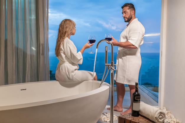 Happy lovely couple caucasian man and woman wearing white housecoat drinking red wine at bathroom with panoramic windows