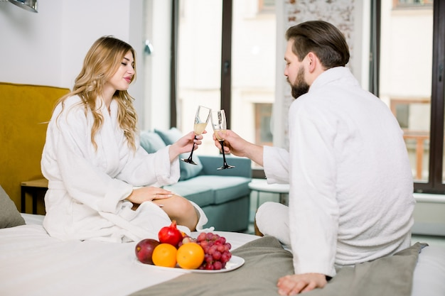 Happy lovely couple caucasian man and woman wearing white housecoat smiling to each other and drinking sparkling wine during breakfast in bed at hotel room