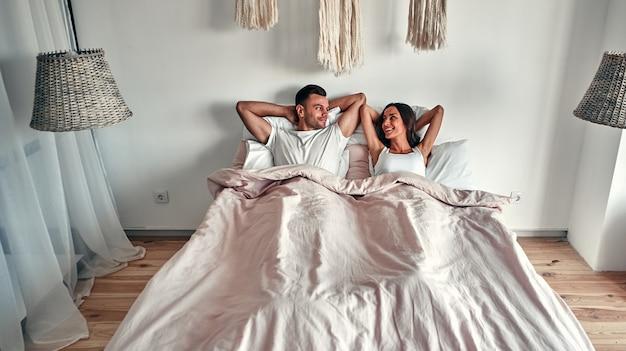 Счастливая милая пара, лежа в постели и улыбаясь. влюбленные, наслаждающиеся близостью и единением. молодожены проводят первую ночь в гостиничном номере, чувствуя волнение