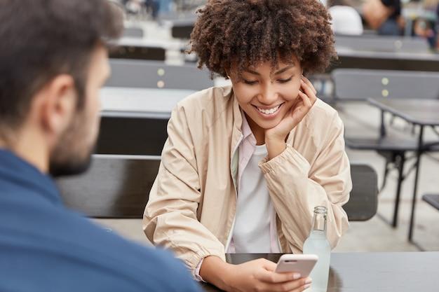 Felice coppia adorabile pongono nel contesto urbano al caffè