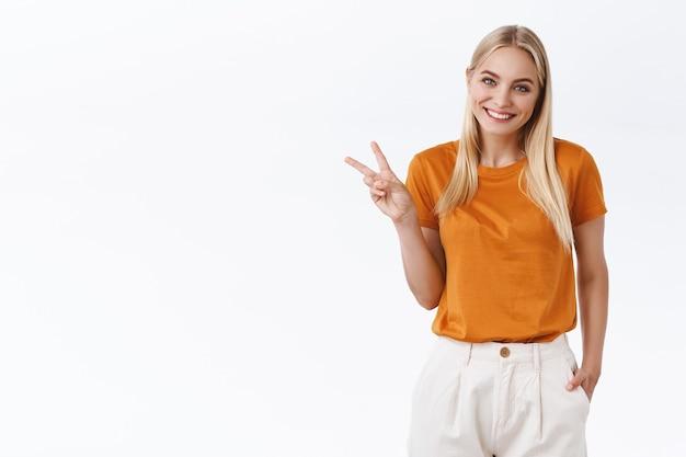 Счастливая, милая женственная стильная блондинка в модных брюках оранжевой футболки, держит руку в кармане, показывает знак мира или победы, как скромная улыбающаяся с милым довольным выражением лица, стоит на белом фоне