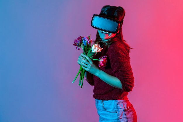 Счастливая милая девушка в гарнитуре очки vr, держа букет цветов и улыбаясь