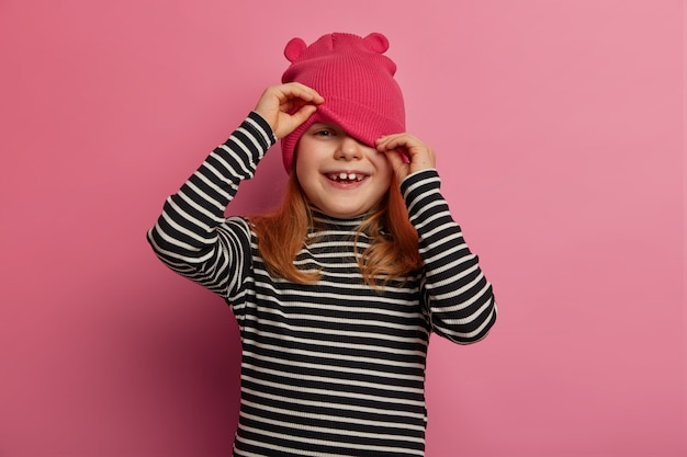 Happy lovely girl preschooler looks from under hat, plays hide and seek, wears casual striped jumper, isolated over rosy pastel wall, has healthy skin, hears hilarious story, laughs positively
