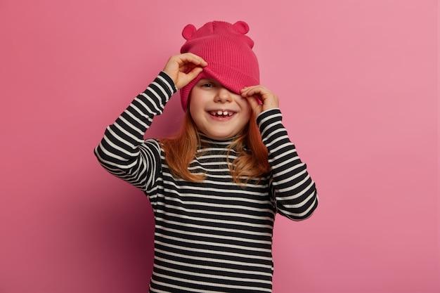 幸せな素敵な女の子の未就学児は帽子の下から見て、かくれんぼをし、カジュアルなストライプのジャンパーを着て、バラ色のパステルカラーの壁に隔離され、健康な肌を持ち、陽気な話を聞き、前向きに笑います
