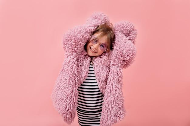 Счастливая милая девушка в стильном меховом фиолетовом пальто и модных круглых очках позирует