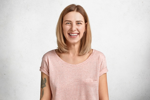 Happy lovely pretty young female model with bobbed hairstyle and shining smile, being in good mood after successful shopping, dressed in casual loose t shirt