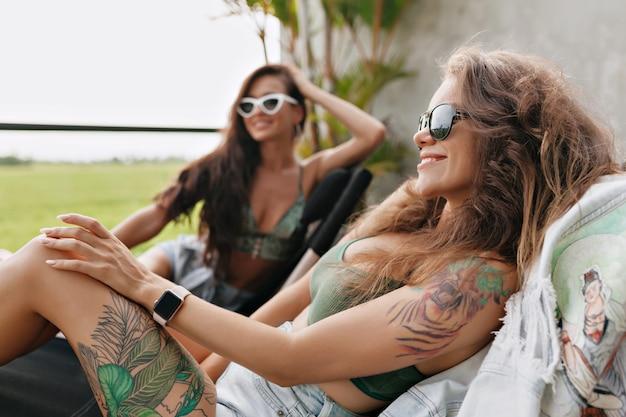 寝椅子に座っているデニムのショートパンツで幸せな素敵なスタイリッシュな女性-夏の屋外テラスで友人と長い間休んでいます