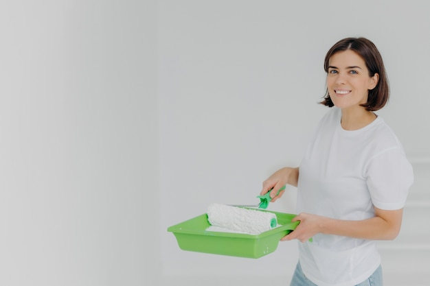 Happy lovely woman in white casual t shirt, poses with paint roller and special tray