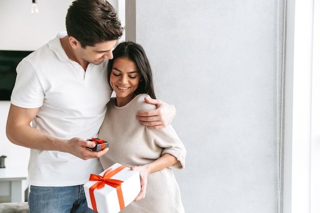 Счастливая прекрасная молодая пара празднует вместе, стоя у себя дома