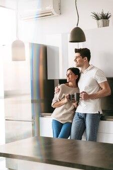 Счастливая милая молодая пара, держащая чашки, стоя на кухне дома