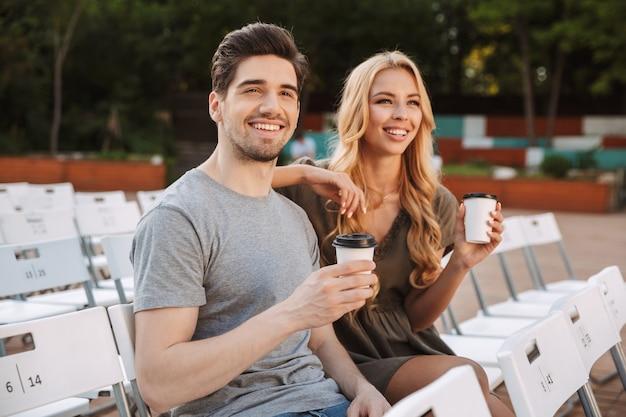 椅子に一緒に座って、屋外でコーヒーと一緒に映画を見ている幸せな素敵な若いカップル