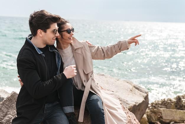 Счастливая милая молодая пара в пальто, сидя на пляже, держась за руки, обнимая
