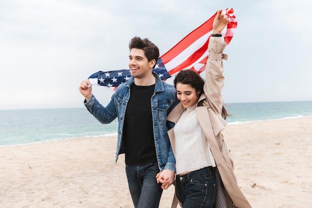 ビーチを歩いて、手をつないで、アメリカの国旗を運ぶコートを着て幸せな素敵な若いカップル
