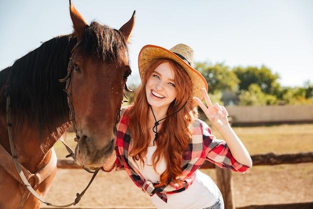 말과 함께 서서 평화 기호를 보여주는 행복 사랑스러운 젊은 여자 카우걸