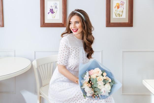 카페에 앉아 꽃의 부케와 흰 드레스에 행복 사랑스러운 젊은 여자
