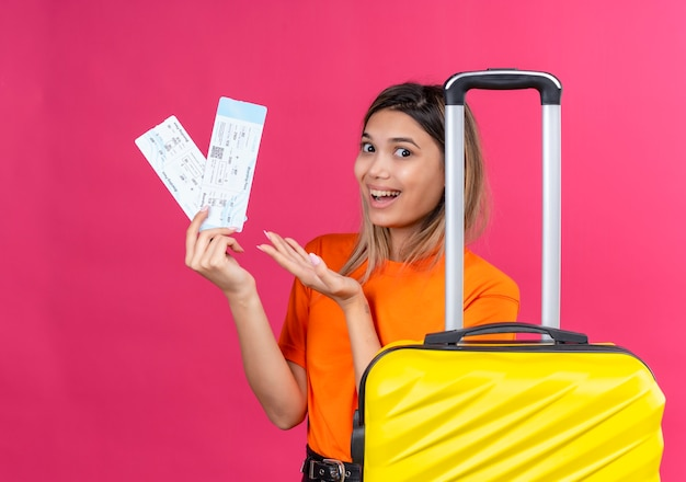 A happy lovely young woman in an orange t-shirt showing plane tickets with yellow suitcase on a pink wall