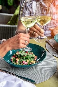 Счастливые любовники, привлекательная женщина и мужчина наслаждаются романтикой. привлекательная пара, делающая селфи, улыбающаяся и весело проводящая время вместе. пара ест салаты, пьет вино с фотографированием.