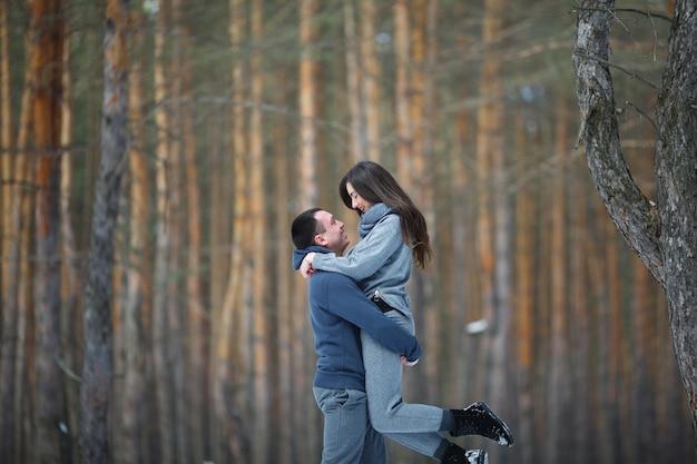 屋外の雪に覆われた森を背景に冬の幸せな恋人たち Premium写真