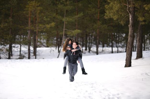 屋外の雪に覆われた森を背景に冬の幸せな恋人たち