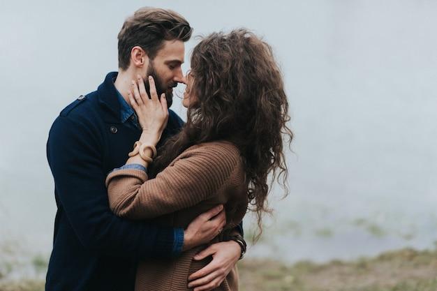 Счастливые влюбленные у озера. молодая пара обнимается в осенний день на открытом воздухе. день святого валентина. понятие о любви и семье.