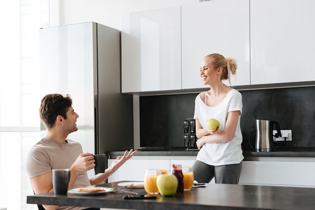 Happy lovers talking while sitting in kitchen in morning