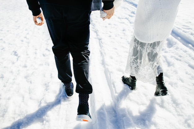 Happy lovers walk together in the snow
