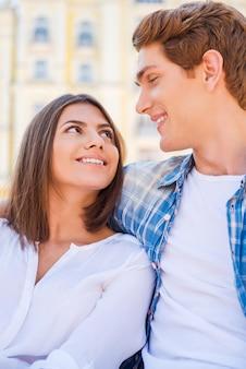 Счастливая любящая пара. красивая молодая влюбленная пара вместе сидит на скамейке и смотрит на каждого