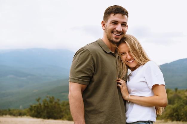 幸せな愛情のあるカップルのハイキングや山での抱擁