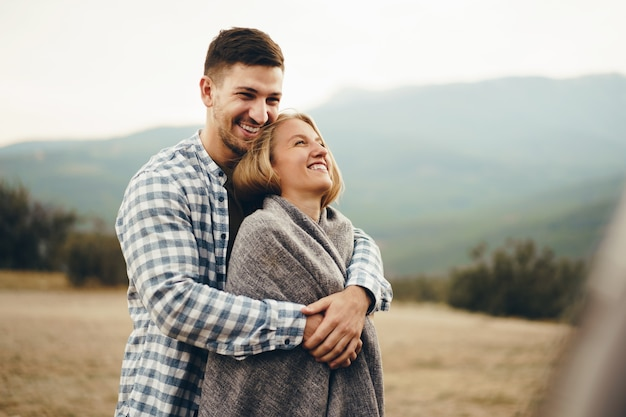 Happy loving couple hiking and hugging in mountains, close up