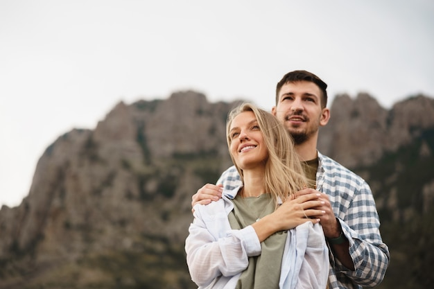 Happy loving couple hiking and hugging in mountains