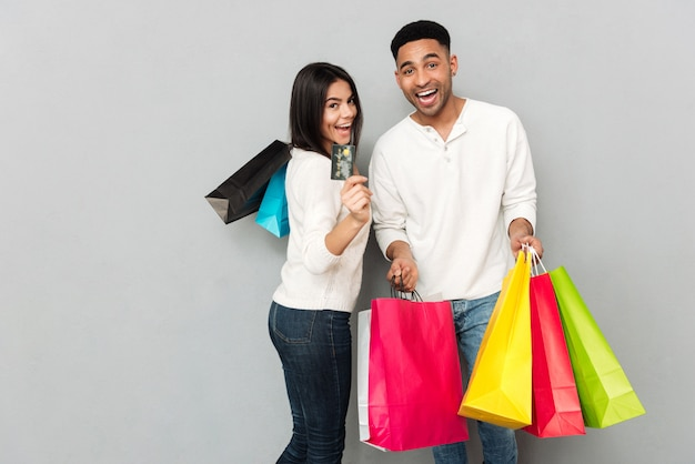 Happy loving couple holding shopping bags and credit card