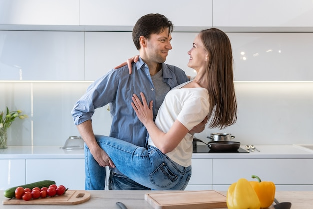 Happy loving couple hugging in the kitchen