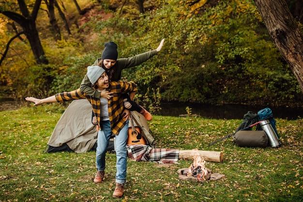 Счастливая влюбленная пара туристов развлекается в лесу возле палатки и делает самолет