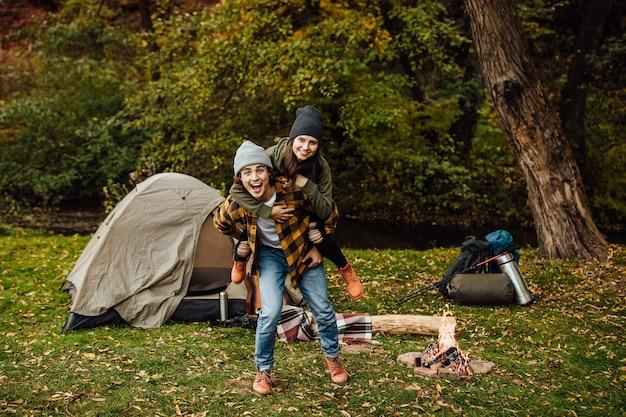 観光客の幸せな愛情のあるカップルは、テントの近くの森で楽しんでいます