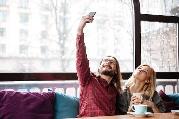 Счастливая любящая пара, сидя в кафе и сделать селфи.