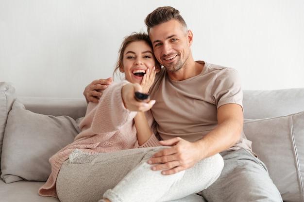 幸せな愛情のあるカップルが一緒にソファに座ってテレビを見て