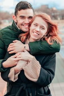 幸せな愛情のあるカップルの笑顔と通りで抱き締めます。 2人の幸せな人々のラブストーリー-ミディアムショットのポートレート