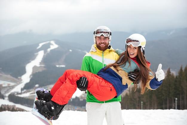 凍るような冬の日の斜面で幸せな愛情のあるカップルのスノーボーダー。カメラを見てください
