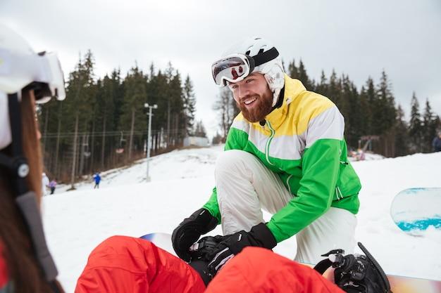 凍るような冬の日の斜面で幸せな愛情のあるカップルスノーボーダー
