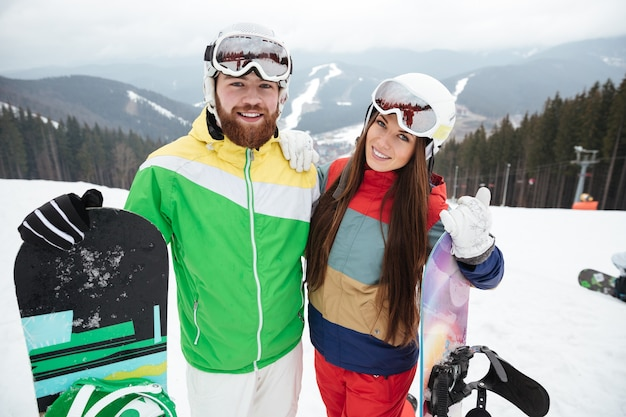 Happy loving couple snowboarders on the slopes frosty winter day