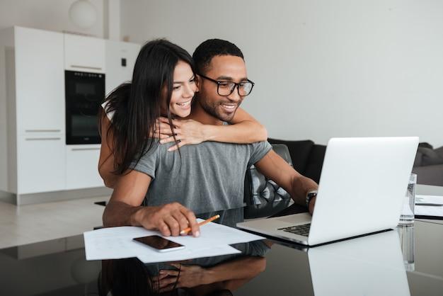 Счастливая любящая пара с помощью ноутбука и анализа их финансов. глядя на ноутбук.