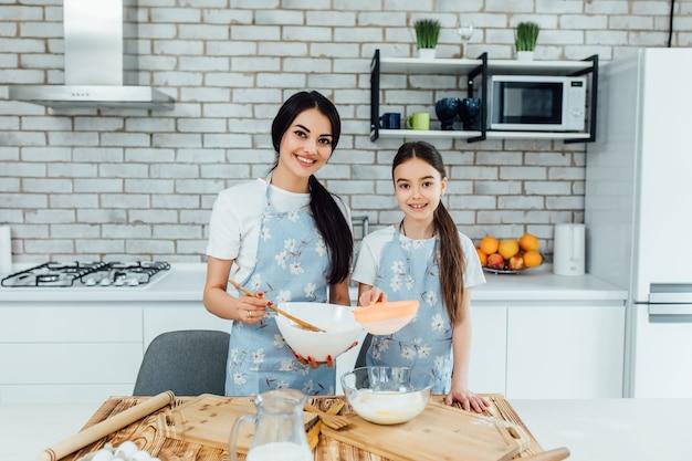 행복한 사랑하는 가족이 밀가루와 계란으로 빵집을 준비하고 있습니다