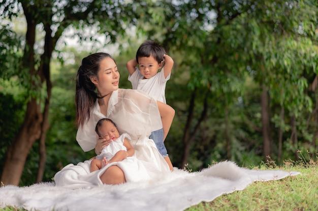幸せな愛情のある家族。アジアの美しい母親と彼女の子供、生まれたばかりの赤ちゃんの少女と公園で遊んで、ハグする芝生の上に座っている少年