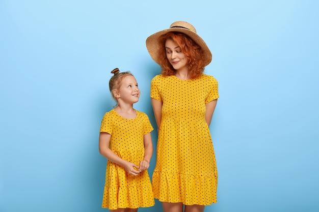幸せな愛情のある家族の概念。ファッショナブルな帽子と黄色のドレスの赤い髪のママ