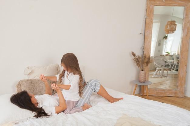 Счастливая любящая семья лежит, отдыхая и наслаждаясь в спальне вместе